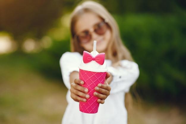 Petite fille, dans parc, debout, à, rose, tasse