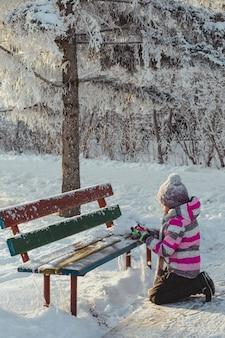 Une petite fille dans le parc fait des boules de neige avec de la neige. concept de jeux de plein air