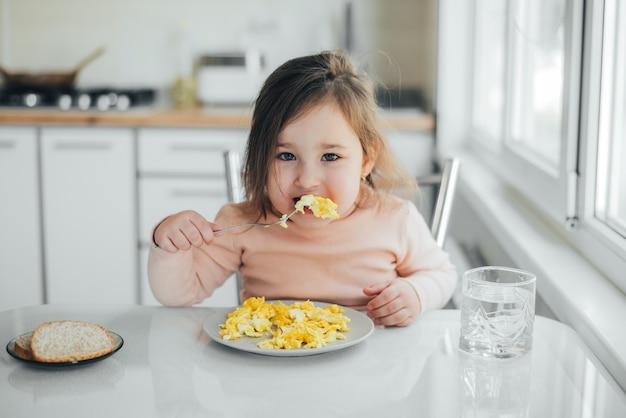 Petite fille dans le pull rose blanc mangeant une omelette