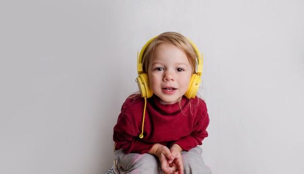 Une petite fille dans un pull rouge écoute de la musique avec des écouteurs et rit sur fond blanc.