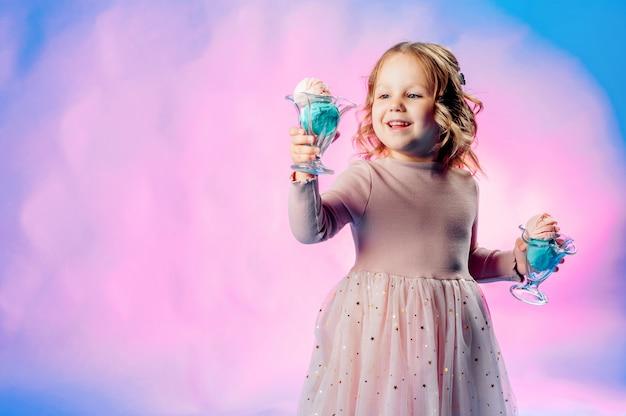 Petite fille dans une robe beige détient 2 boules de crème glacée dans ses mains sur un fond bleu et sourit