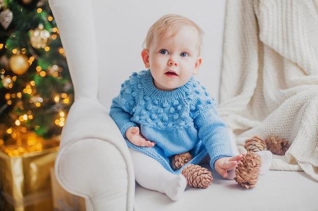 Une petite fille dans une robe bleue tricotée est assise sur une chaise blanche avec des cônes de sapin sur l'arbre de noël