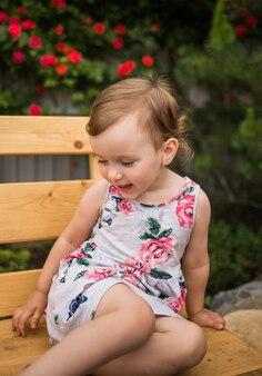 Petite fille dans une robe colorée est assise sur un banc contre la surface d'une rose en fleurs