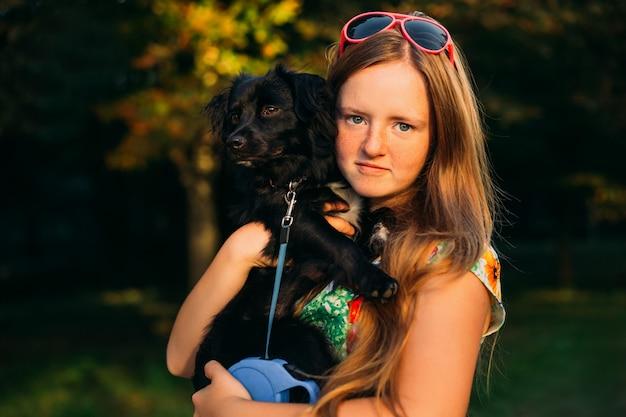 Petite fille dans une robe d'été embrassant son chien noir avec amour