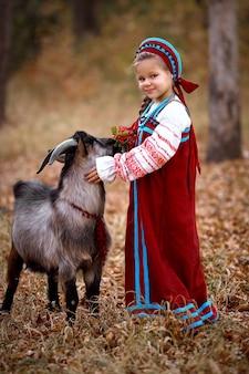 Une petite fille dans une robe d'été rouge se tient à côté d'une jeune chèvre noire dans la forêt d'automne