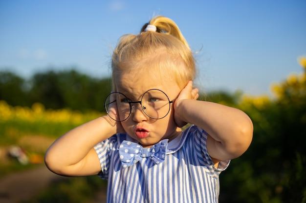 Petite fille dans une robe et des lunettes sur le fond d'un champ de tournesol. visage émotionnel.