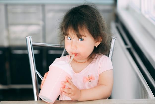 Une petite fille dans une robe rose boit dans un verre à cocktail rose assis dans la cuisine drôle