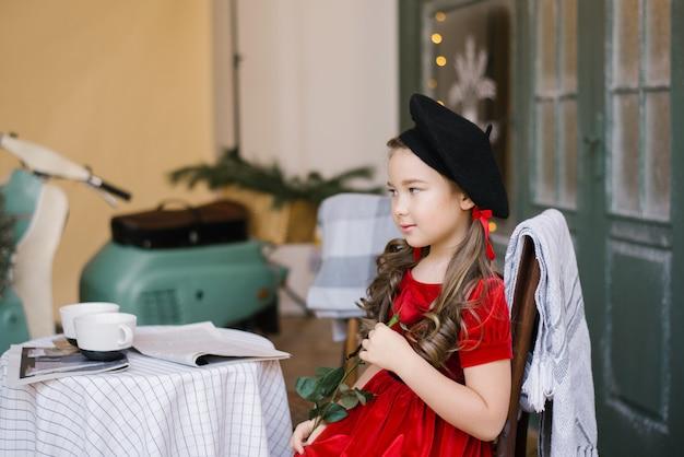 Petite fille dans une robe en velours rouge et un béret noir assis à une table de café, tenant une rose rouge