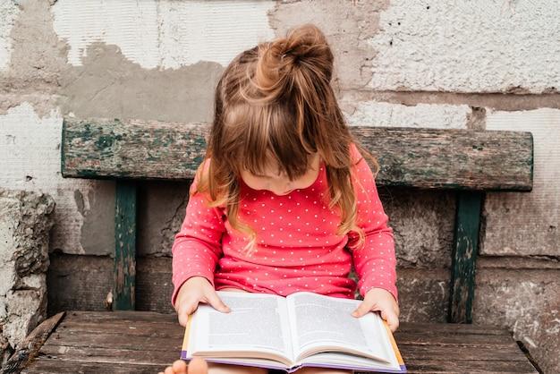 Petite fille dans un rouge sur l'herbe verte et lire un livre dans une journée d'été ensoleillée.