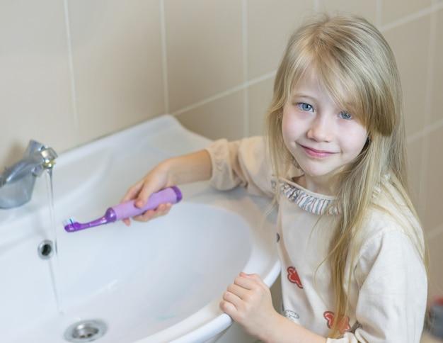 Une petite fille dans la salle de bain lave une brosse à dents électrique.