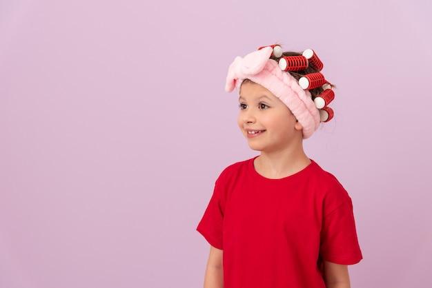 Une petite fille dans un t-shirt rouge avec des bigoudis sur la tête sourit.