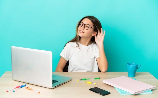 Petite fille dans une table avec un ordinateur portable sur fond bleu isolé écoutant quelque chose en mettant la main sur l'oreille