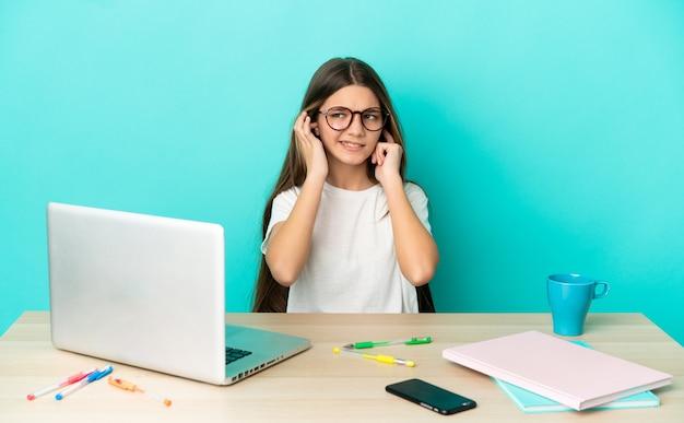 Petite fille dans une table avec un ordinateur portable sur fond bleu isolé frustré et couvrant les oreilles