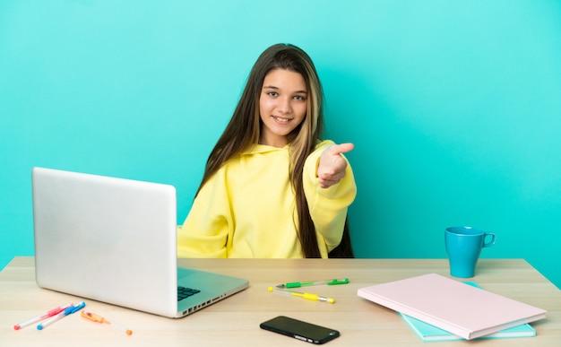 Petite fille dans une table avec un ordinateur portable sur fond bleu isolé se serrant la main pour conclure une bonne affaire
