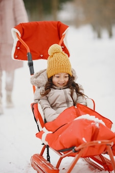 Petite fille dans un traîneau sur le parc enneigé