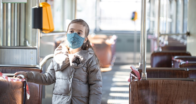 Une petite fille dans un transport public vide pendant la pandémie de coronavirus.