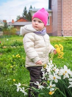 Petite fille dans une veste chaude et un chapeau rose recueille des pissenlits jaunes
