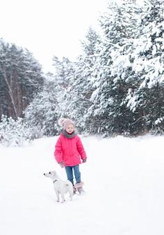 Petite fille dans une veste lumineuse joue dans la forêt enneigée d'hiver avec son chien jack russell terrier