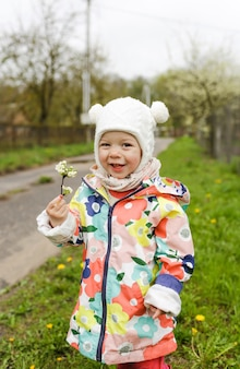 Une petite fille dans une veste lumineuse rit joyeusement dehors au printemps et tient une branche avec des fleurs blanches printanières. le bonheur des enfants.