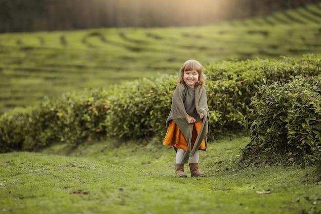 Petite fille dans des vêtements chauds dans le domaine avec des plantes d'arbre à thé