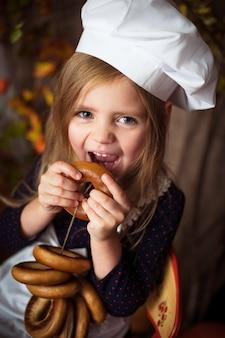 Petite fille dans des vêtements de cuisine avec des bagels dans ses mains et souriant