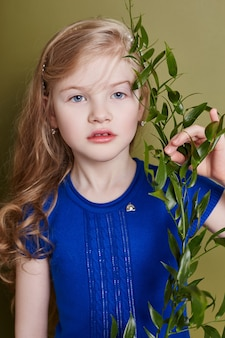 Petite fille dans des vêtements de printemps lumineux. regard romantique et sourire sur ton visage