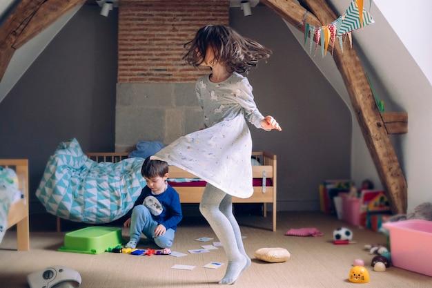 Petite fille dansant avec bonheur et jouant avec son frère à la maison