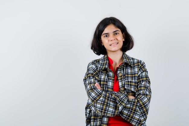 Petite fille debout avec les bras croisés en chemise, veste et à l'optimisme. vue de face.