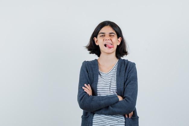 Petite fille debout avec les bras croisés, qui sort la langue en t-shirt