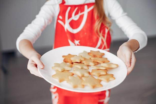 Petite fille debout dans une cuisine avec des cookies