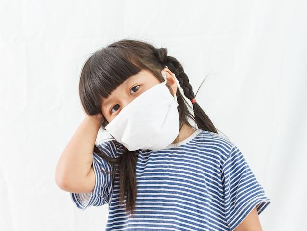 Petite fille debout dans un masque de protection, masque blanc, fille debout sur fond blanc