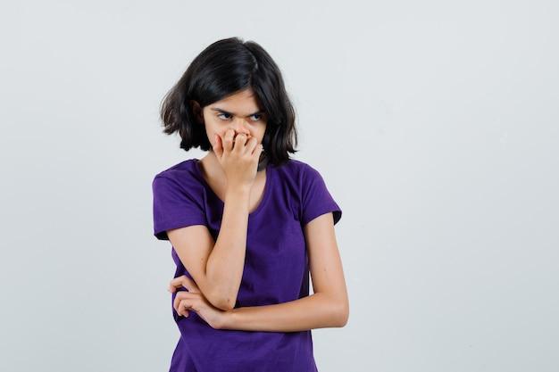 Petite fille debout dans la pensée pose en t-shirt et à la déprimée.