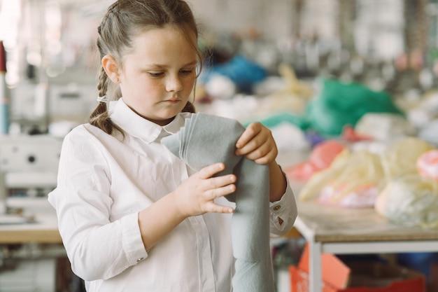 Petite fille debout dans l'usine avec un fil