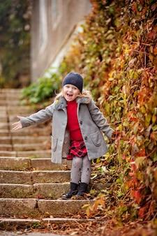 Petite fille debout sur une marche dans le parc, bébé heureux