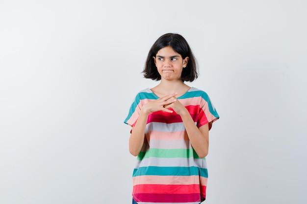 Petite fille debout en pensant pose en t-shirt et à la vue douteuse, de face.