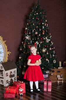 Petite fille debout près de l'arbre de noël et cadeau