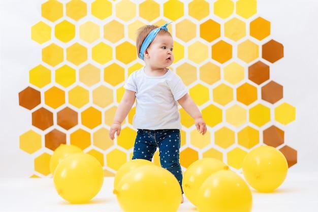 Une petite fille debout sur un sol blanc avec des ballons jaunes. en arrière-plan, des nids d'abeilles jaunes. journée mondiale des enfants.