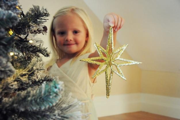 Petite fille décorant l'arbre de noël à la maison