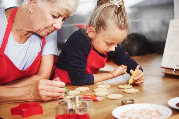 Petite fille décorant des cookies avec sa grand-mère