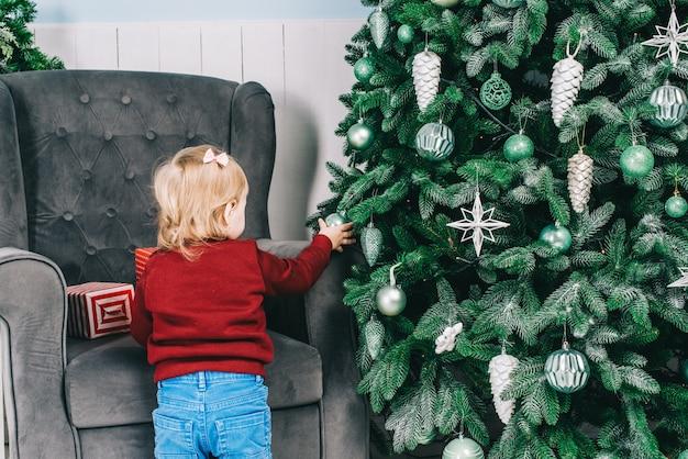 Une petite fille décore un sapin de noël