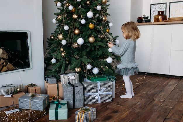 Petite fille décorer un arbre de noël à la maison
