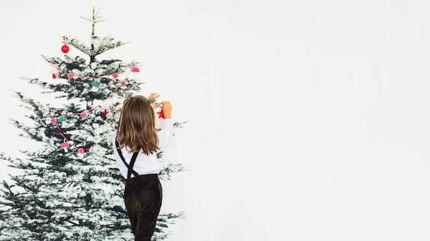 Petite fille à décorer le sapin de noël
