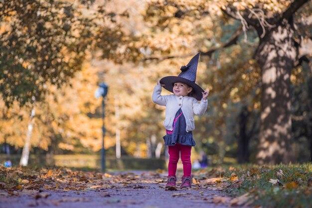 Petite fille déguisée en sorcière avec un chapeau d'halloween dans un parc tombé jaune ensoleillé