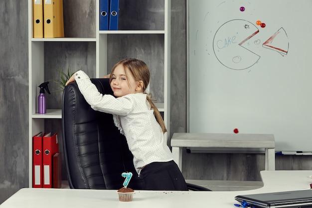 Une petite fille dépeint un employé de bureau, qui tourne au ralenti et agit en travaillant