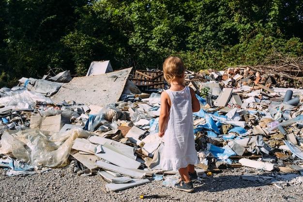 Petite fille à un dépotoir parmi un tas d'ordures éparpillées dans la forêt
