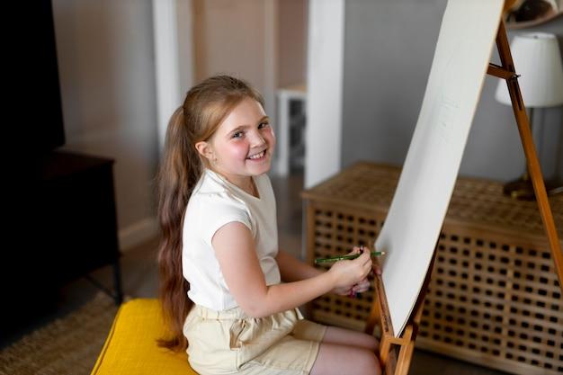Petite fille dessin à l'aide de chevalet