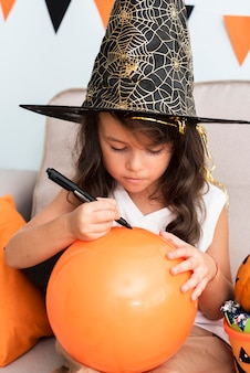 Petite fille dessinant un ballon d'halloween