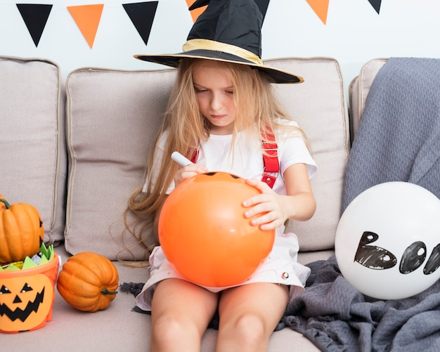 Petite fille dessinant un ballon d'halloween