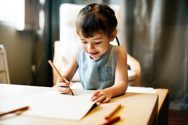 Petite fille dessinant dans un livre