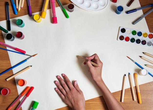 Petite fille dessinant sur fond de papier vierge
